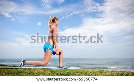 Blond female warms up with dumbells
