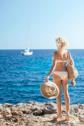 Blond fit woman alone in white bikini standing on a rocky seacoast, holding straw summer hat and straw bag looking at boat far away at sea and enjoy nature back shot. Summertime, sea voyage, holidays.