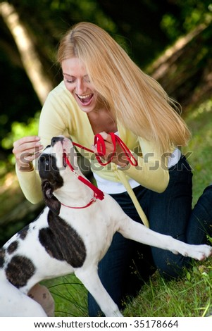 Blond girl and a American bulldog in the park