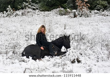 blond girl and her black stallion laid down in the snow