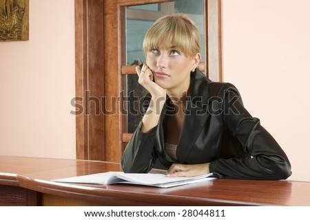 blond girl at  front desk of Hotel reception lost in thought