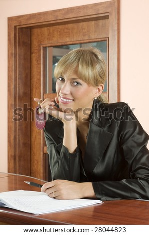 blond girl at hotel reception smiling keeping and the key in hand