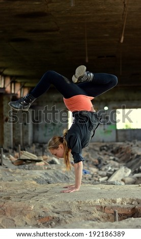 Blond girl dancing break dance in the old brickworks