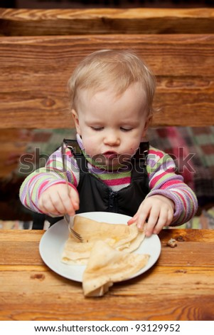 Blond girl eating delicious pancakes on white plate