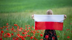 Blond girl holding flag of Poland in the poppy field. Back view. Polish Flag Day. Independence Day. Travel and learn polish language concept. Selective focus.
