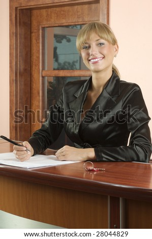 blond girl Hotel reception in black suit smiling