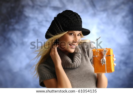 Blond girl in a hat with a gift