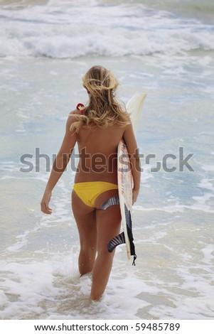 blond girl in a yellow bikini with her surfboard