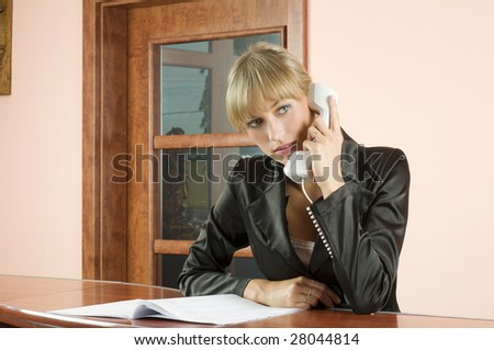 blond girl in Hotel reception talking at telephone