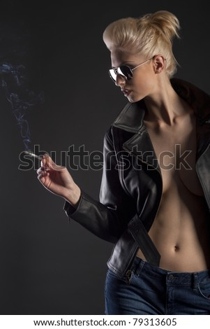 Blond girl in leather jacket and jeans with sunglasses and cigarette