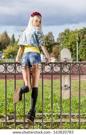Blond girl in short shorts and denim coat with roses wreath on head turns back having climbed fence with skateboard hung on it