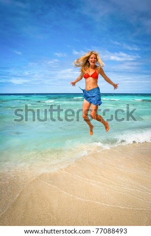 Blond girl jumping on the beach, Polynesia