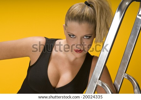 Blond girl leaning on aluminum ladder on yellow background
