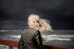 Blond girl looking at stormy sea. Dark sky in in the background. Selective focus.