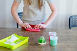 blond girl playing with pink slime in her hands at home , selective focus