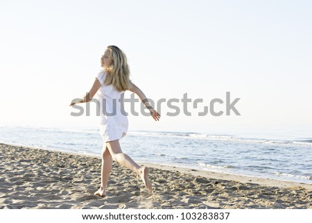 Blond girl running along the shore on a beach with a blue sky in the background.