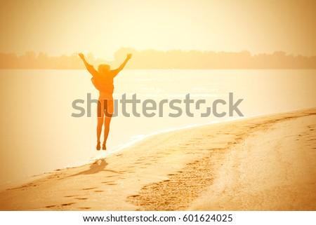 Blond girl teenager jumping up on the beach in the sunshine