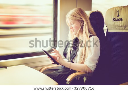 blond girl traveling in first class of a german train, toned image, selective focus