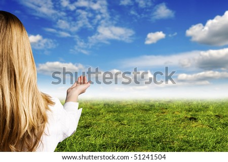 blond girl with an open hand, with blue sky and green meadow in background