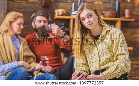 Blond girl with big eyes in yellow vintage shirt sitting in living room of countryside wooden cottage. Bearded man and his wife chatting, drinking and having fun while their daughter sits alone. #1397772557