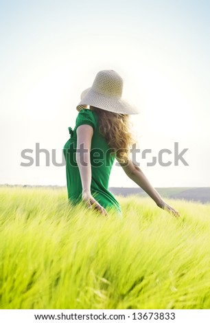 blond girl with big hat walking through a green wheat field against blue sky