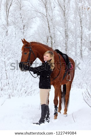 Blond girl with her horse in a snow landscape