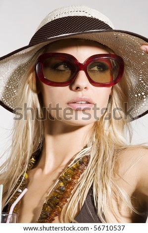 blond girl with summer hat and sunglasses posing and taking sun