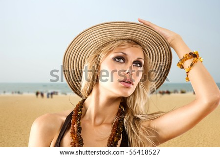 blond girl with summer hat on the beach with yellow warm sand