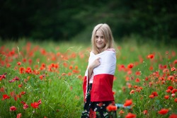 Blond girl wrapped in flag of Poland in the poppy field. Polish Flag Day. Travel and learn polish language concept.