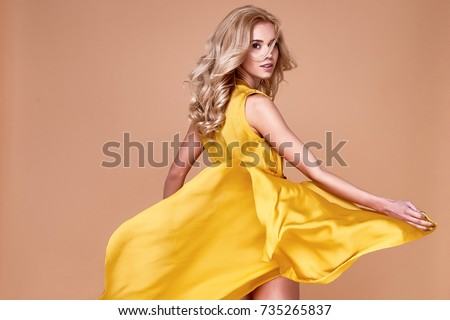 Blond hair woman beautiful face sexy skinny body shape tan skin care wear fashion dress silk yellow color runway model studio catalog clothes style for summer vacation walk date beach party makeup.