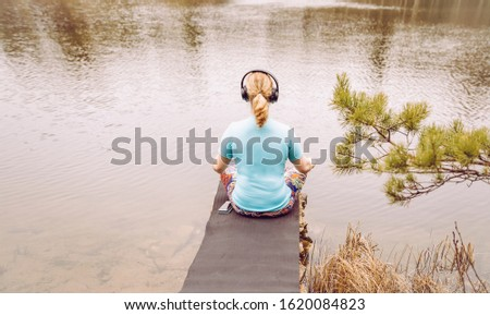 Blond hair woman sit outdoors by water and listen audio guided meditation from smartphone, wearing blue T-shirt sports clothing. Warm sunny day.