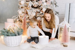 Blond Hair Young Boy and blond pretty woman enjoying Christmas Time opening gifts under Christmas tree
