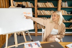 Blond haired businesswoman sitting at the desk in home office, looking at office blackboard, smiling. Freelancer holding online conference, learning graphs, distant work concept