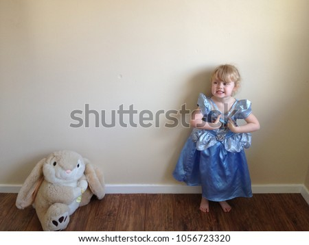 Blond haired girl plays dress up as  Disney princess with Easter rabbit soft toy