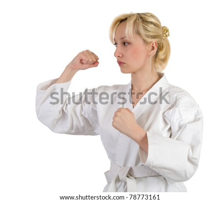 Blond in a kimono in karate pose isolated on white background.