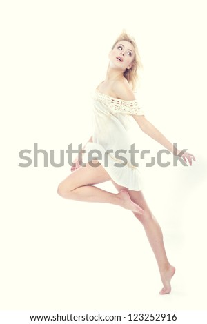 Blond lady dancing on a studio background