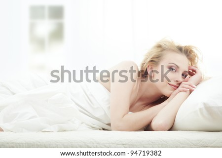 Blond lady laying in bedroom at early morning
