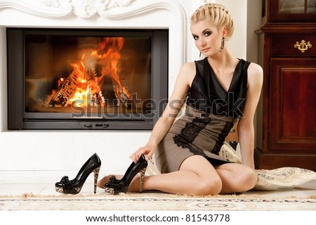 Blond lady near fireplace