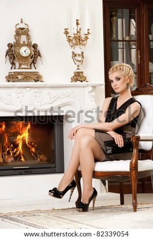Blond lady near fireplace in a luxury interior