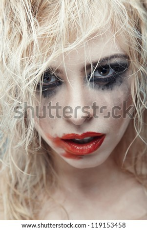 Blond lady with strange makeup. Vertical photo