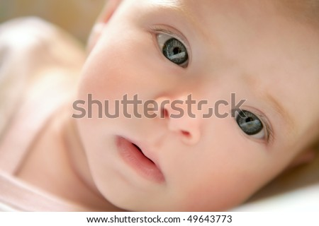 Blond little baby laying on bed portrait horizontal image