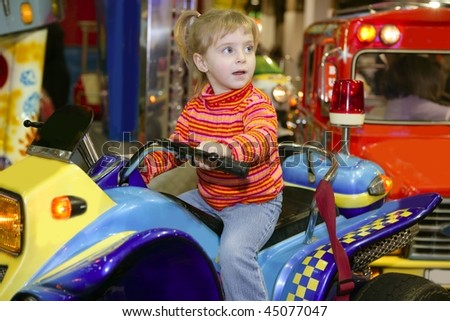 blond little girl in funfair fairground attraction car