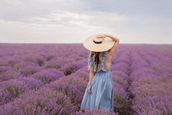 Blond long haired girl in lavender field under the rain in straw hat and blue long dress on cloudy windy day