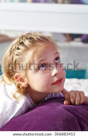 Blond pensive girl in bed thinking in her nursery