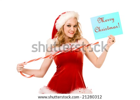 "Blond sensual pinup woman in Christmas Mrs Santa Claus outfit holding sheet of paper with text ""Merry Christmas"" and points to it by huge candy cane stick. Can be used as greeting card."