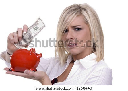 blond stuffing $100 bill into a tiny piggy bank