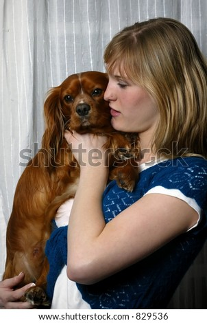 blond teenage girl holding pet king charles spaniel