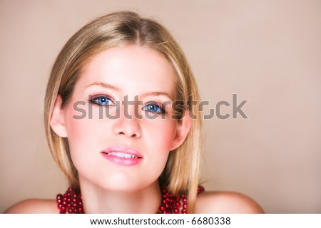 Blond teenage girl with loose straight hair on beige background with red shiny necklace and soft smile. Natural make-up,  has skin texture.