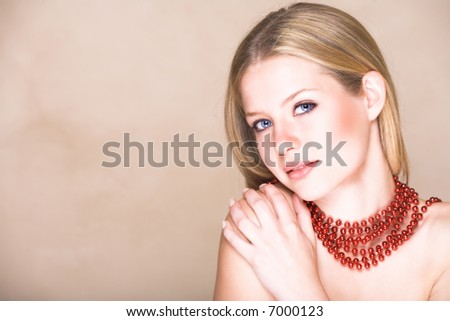 Blond teenage girl with loose straight hair on beige background with red shiny necklace and soft smile. Natural make-up