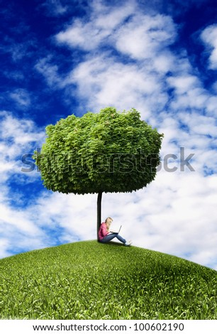blond teenager girl sitting under a tree with laptop